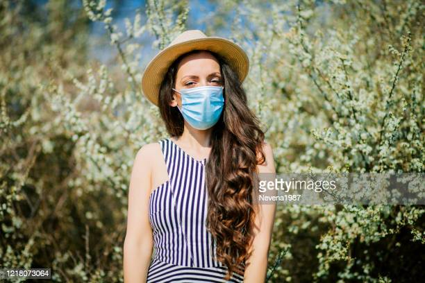 young woman in protective mask near blooming tree. allergy concept - nose mask stock pictures, royalty-free photos & images