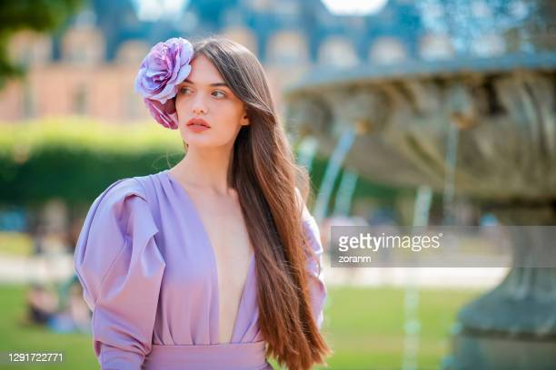 young woman in purple dress and flower fascinator by the fountain - fascinator stock pictures, royalty-free photos & images