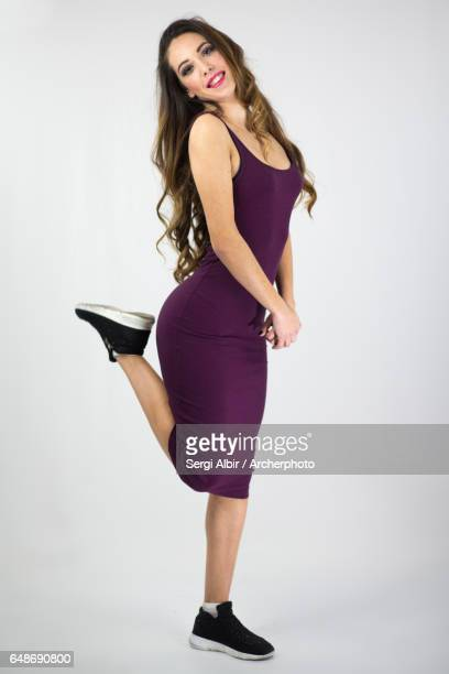 Young woman in purple dress in a happy pose