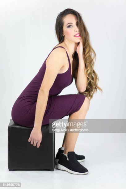 Young woman in purple dress with great hair sitting and smiling