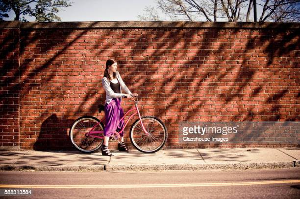 young woman in purple skirt with bicycle on sidewalk against brick wall - purple skirt stock pictures, royalty-free photos & images