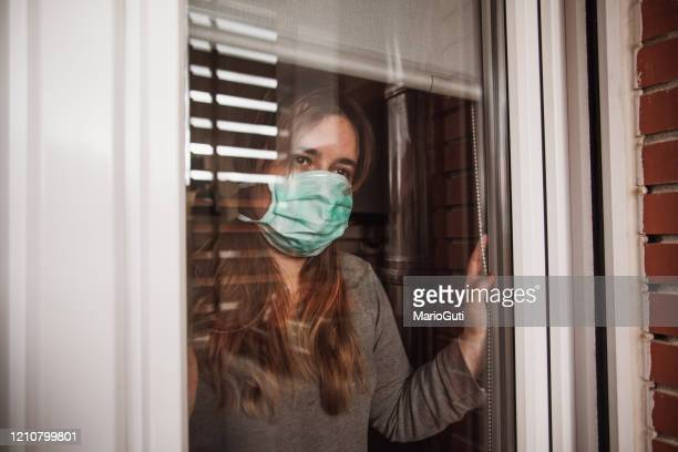 young woman in quarantine wearing a mask and looking through the window - spain stock pictures, royalty-free photos & images