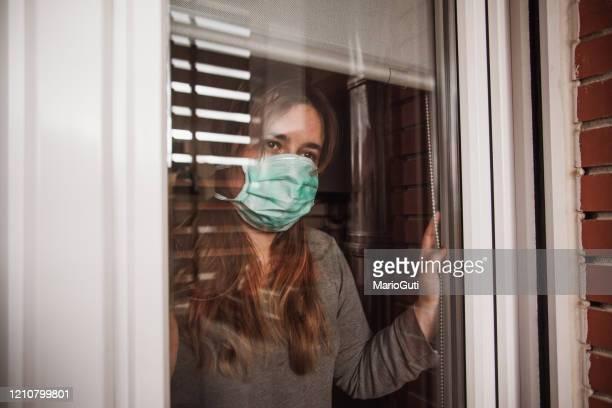 jonge vrouw in quarantaine die een masker draagt en door het venster kijkt - spanje stockfoto's en -beelden