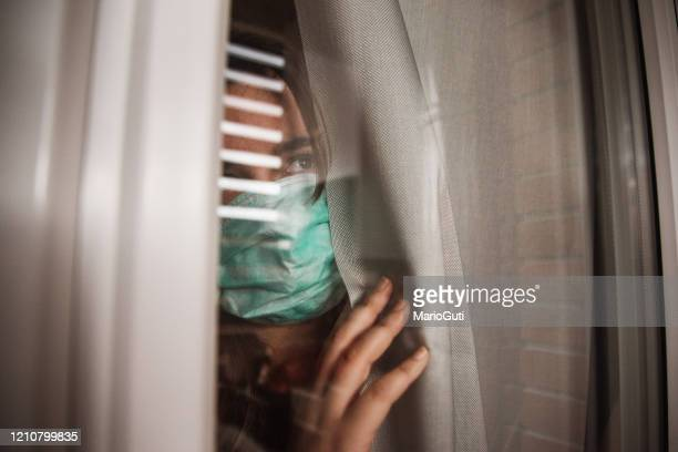 young woman in quarantine wearing a mask and looking through the window - isolamento foto e immagini stock