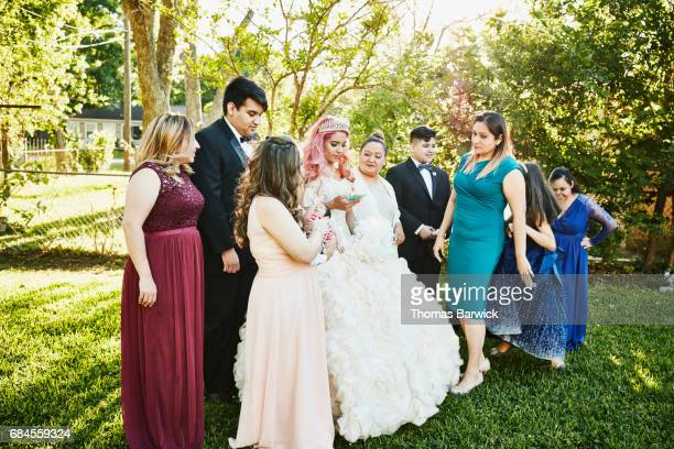 young woman in quinceanera gown looking at smartphone while standing with family in backyard - 14 15 anni foto e immagini stock