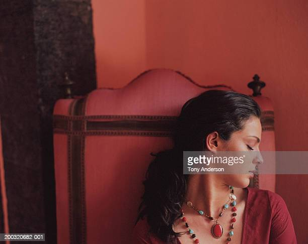 Young woman in red chair, eyes shut, close-up