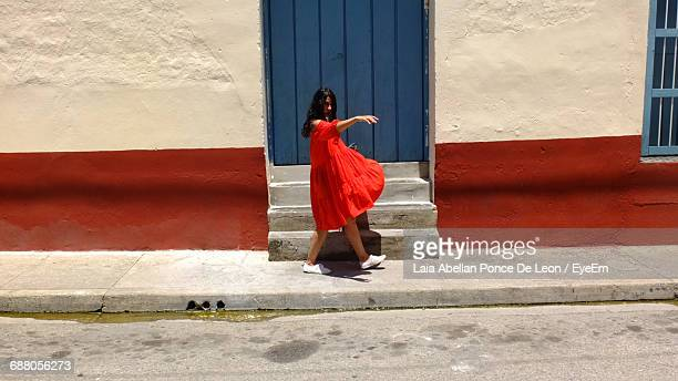 Young Woman In Red Dress Dancing On Sidewalk