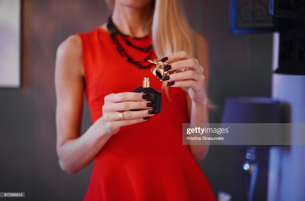 young woman in red dress holding a bottle of perfume : ストックフォト