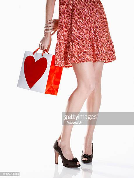 Young woman in red dress holding shopping bag (low section)