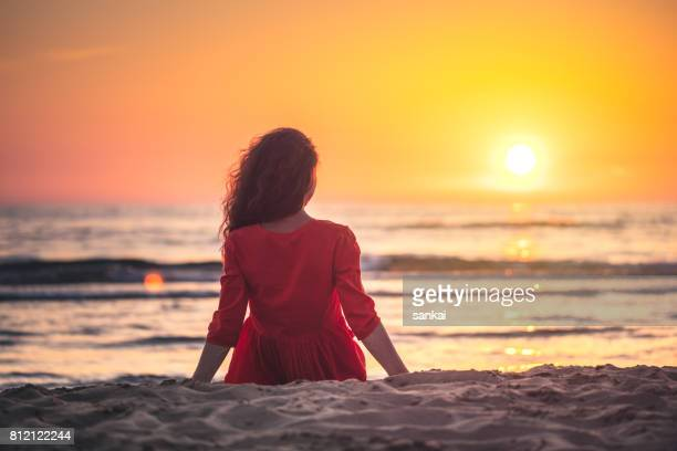 Young woman in red dress sits on a beach enjoys view of sunset over sea