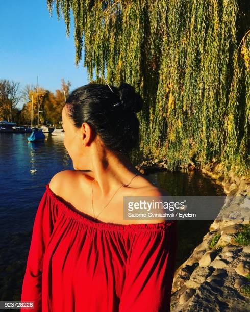 Young Woman In Red Dress Standing At Lake