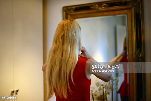 young woman in red dress standing in front of a mirror