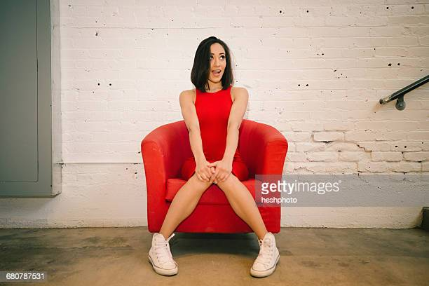 Young woman in red on red armchair
