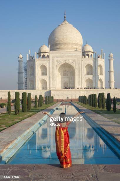 Young woman in red sari in front of Taj Mahal