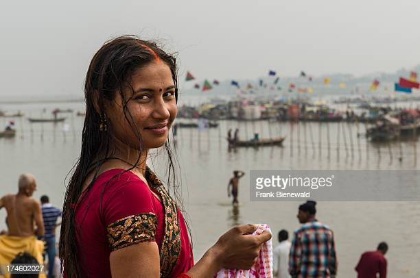 Young woman in red sari smiling at the Sangam the confluence of the rivers Ganges Yamuna and Saraswati at Kumbha Mela many boats in the back