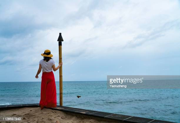 Young woman in red skirt and hat ,looking the sea