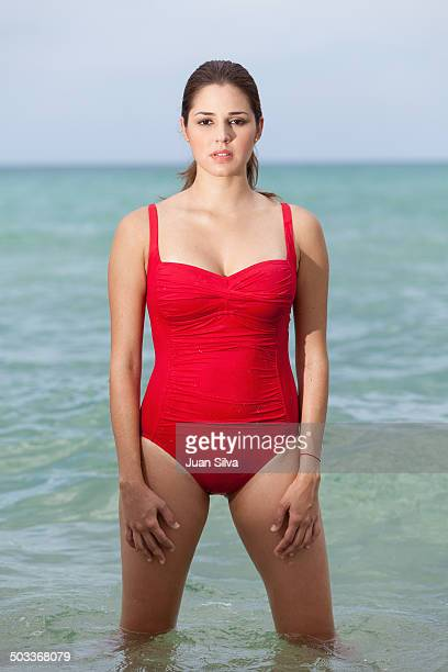 Young woman in red swimsuit in the water at beach