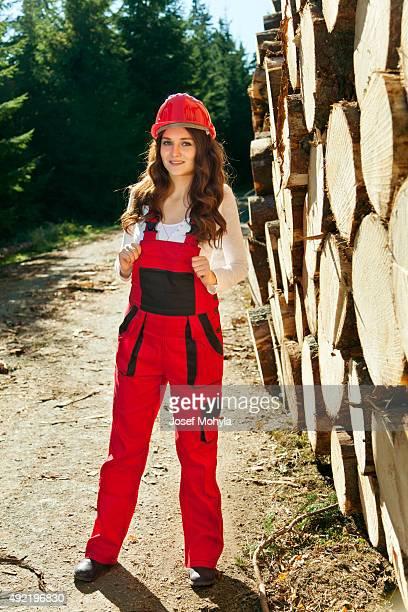 Young woman in red working overalls and helmet outdoors