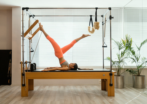Young woman in reformer fitness exercise - gettyimageskorea