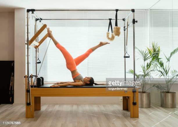young woman in reformer fitness exercise - pilates foto e immagini stock
