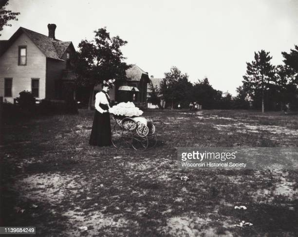 Young woman in residential area standing in a yard pushing a baby carriage with a ruffled top Black River Falls Wisconsin 1894 On the left are houses...