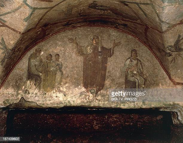 Young woman in rich robes and veiled hood with arms outstretched in prayer on the sides scenes from the life of the deceased lunette fresco Cubicle...