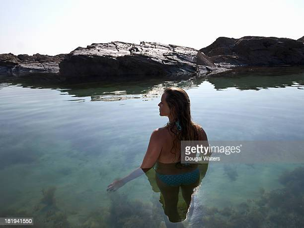Young woman in rock pool.