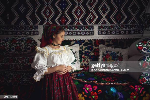 young woman in romanian clothing standing at home - rumania fotografías e imágenes de stock