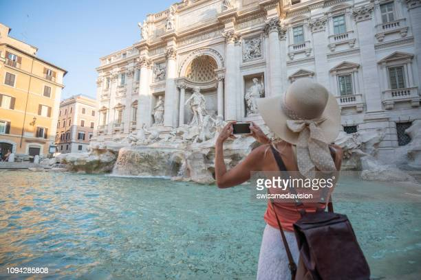 young woman in rome enjoying travel in italy and capturing a photo of the trevi fountain using her smart phone - trevi fountain stock photos and pictures