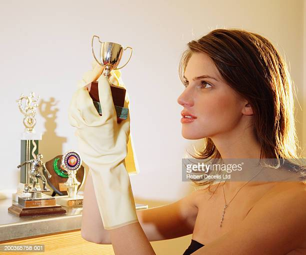 Young woman in rubber gloves polishing trophy, side view, close-up