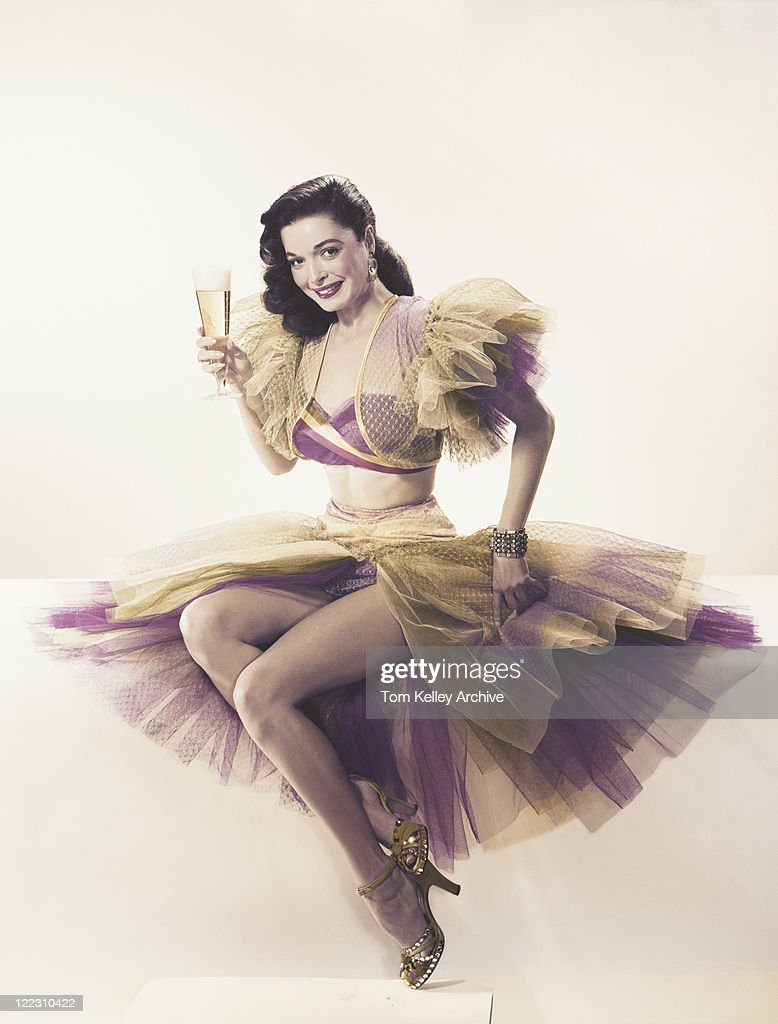 Young woman in ruffled dress holding beer glass, portrait : Stock Photo