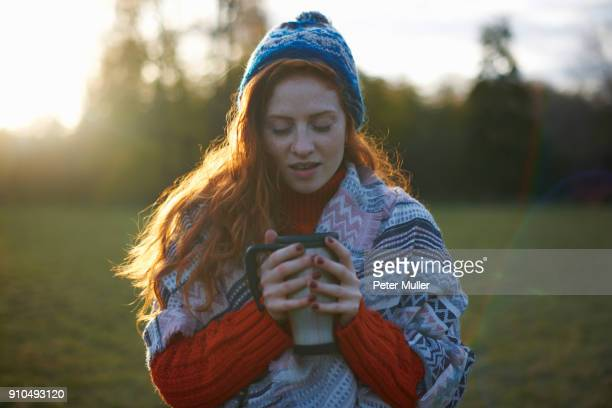 Young woman in rural setting, wrapped in blanket, holding hot drink