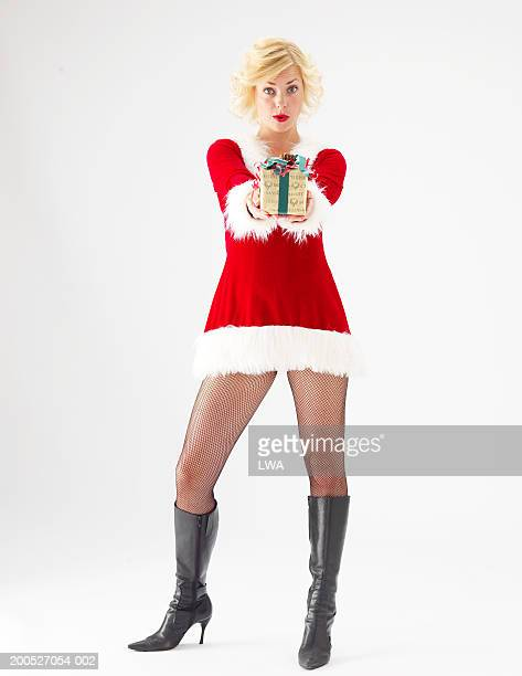 Young woman in Santa suit giving gift, portrait