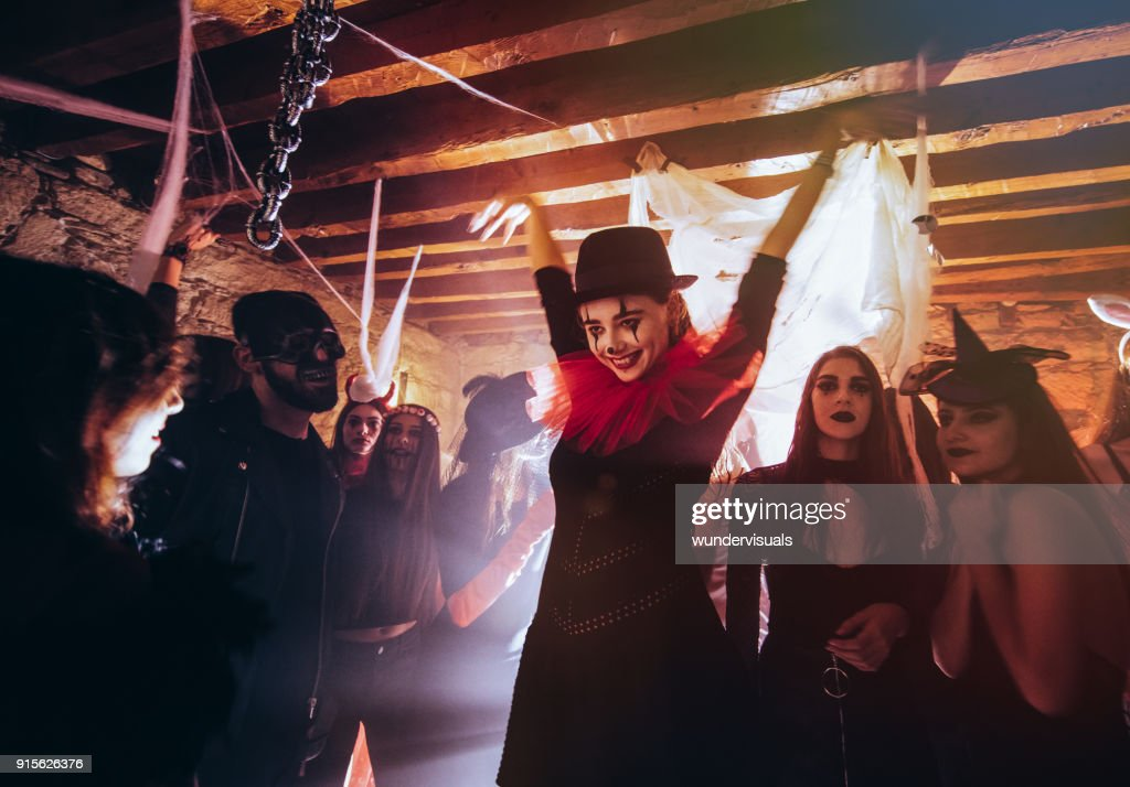 Young woman in scary clown costume dancing at Halloween party : Stock Photo