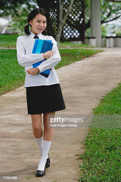 young woman in school uniform, walking on path, smiling at camera - school girl shoes stock pictures, royalty-free photos & images