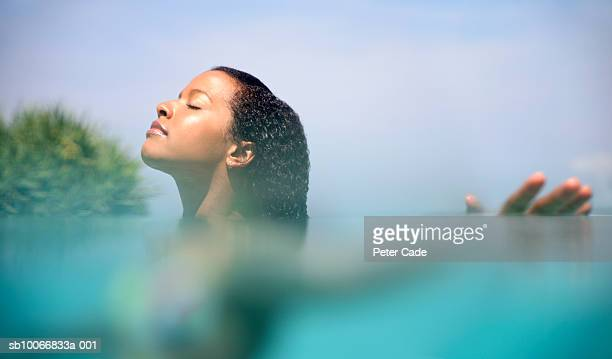 Young woman in sea with arms outstretched