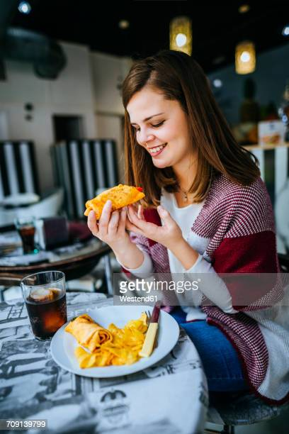 young woman in sevilla eating a burrito - burrito stock pictures, royalty-free photos & images