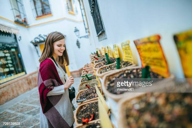 Young woman in Sevilla looking at spice shop