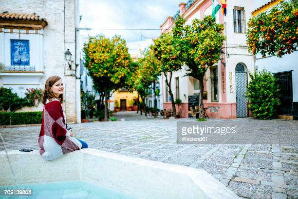 Young woman in Sevilla sitting on fountain at a typical square