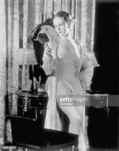 Young woman in sexy negligee standing at makeup table looking at herself in a handheld mirror 1949