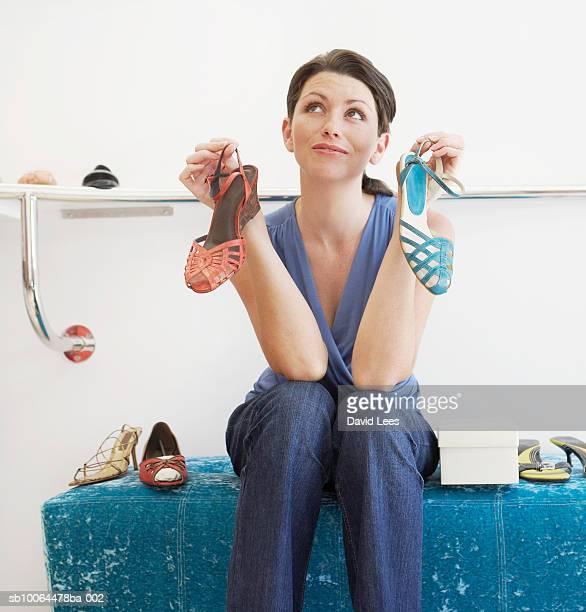 young woman in shoe shop holding two sandals, looking up - sandaal stockfoto's en -beelden