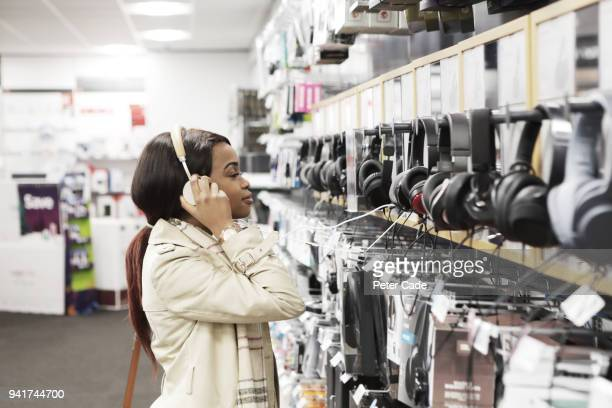 young woman in shop looking at headphones - electronics store stock pictures, royalty-free photos & images
