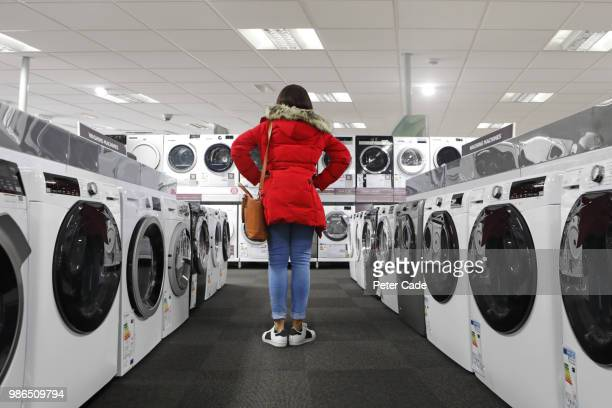 Young woman in shop looking at kitchen appliances