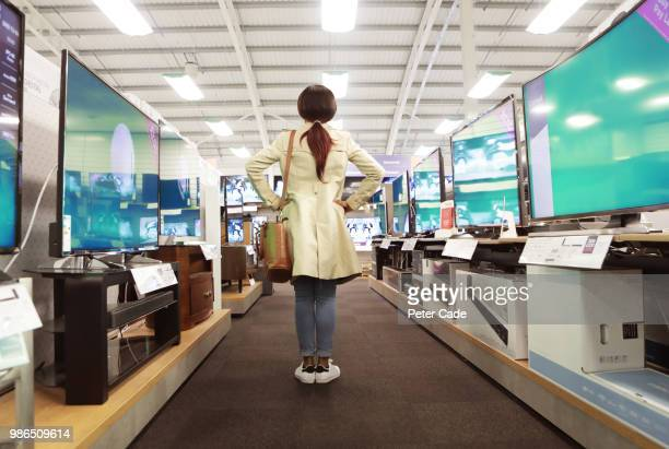 Young woman in shop looking at televisions