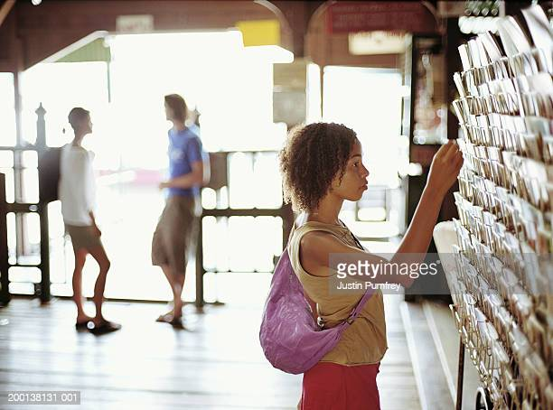 young woman in shop selecting item from rack - postcard stock pictures, royalty-free photos & images