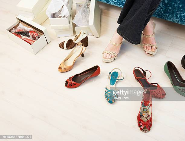 young woman in shop trying on shoes, low section - schoen stockfoto's en -beelden