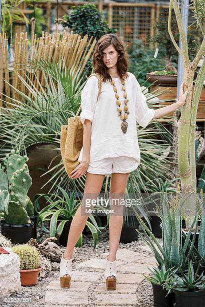 a young woman in shorts and shirt, in platform heels carrying a basket.  - one young woman only stock pictures, royalty-free photos & images