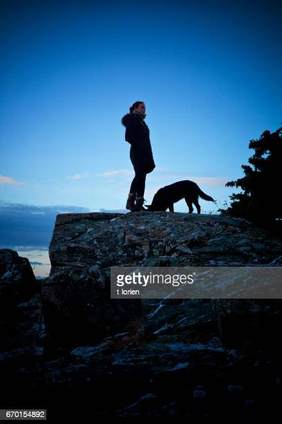 Young woman in silhouet with her dog.