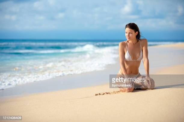 young woman in sitting on the beach - hot model indonesia stock pictures, royalty-free photos & images