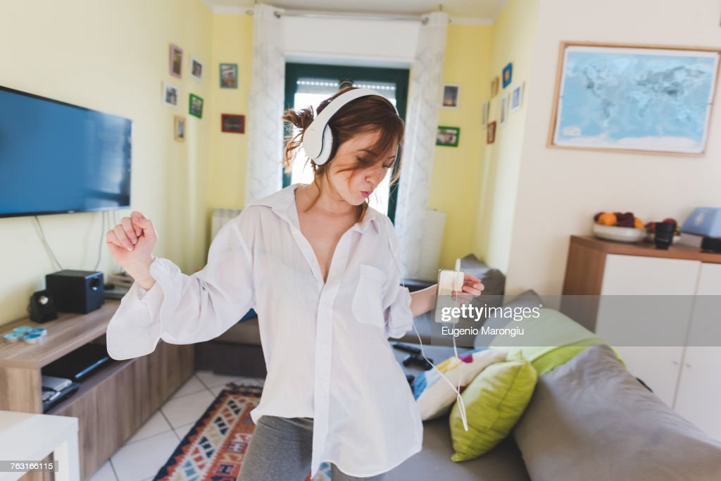 Young woman in sitting room dancing to smartphone music on headphones : Stock Photo